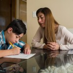 Julie Rodriguez works on homework with her son at their home this fall. After moving from the suburbs last year, Rodriguez says she has struggled to get her son the support he needs at his Chicago Public School.