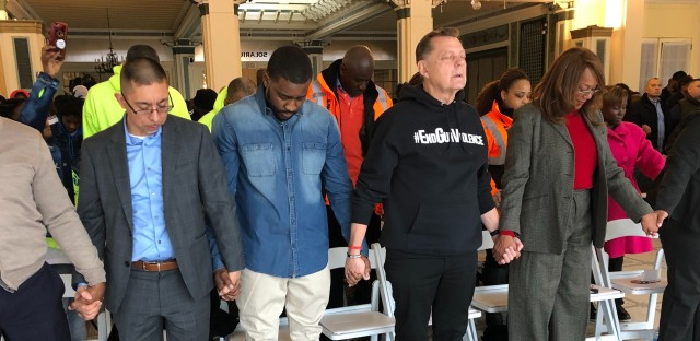 Eddie Bocanegra from READI Chicago, Walter McGee, a Chicago CRED participant, Fr. Michael Pfleger from Saint Sabina Church and Ald. Leslie Hairston hold hands in prayer at an anti-violence event at the South Shore Cultural Center on Tuesday. A coalition of nonprofits is calling for a 20% reduction in homicides in 2020.