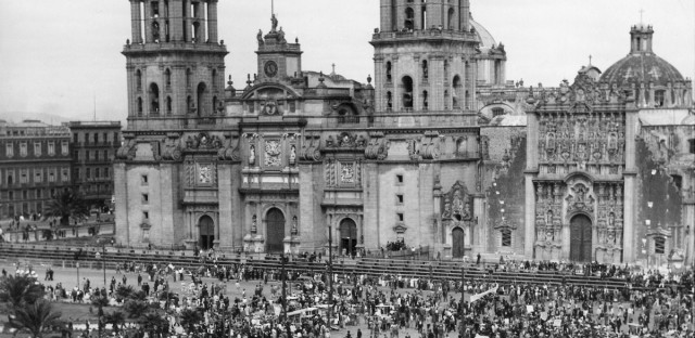 On the 26th anniversary of the revolution that ended Porfirio Diaz' 30-year dictatorship, a huge mass meeting is held by Mexican laborers in front of Mexico City's ancient cathedral on Nov. 23, 1936. Speakers are denouncing fascism.