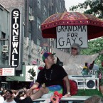 "E.G. Smith, left, and his mother, Norma Isaacs, 88, sitting under an umbrella with a sign that reads, ""Grandma For Gays,"" ride past the site of the original Stonewall Inn in New York's Greenwich Village during the annual Gay and Lesbian Pride Parade on Sunday, June 25, 1989. A record 150,000 people marched down Fifth Avenue, commemorating the 20th anniversary of the Stonewall Inn riots which gave birth to the gay rights movement. (AP Photo/Sergio Florez)"
