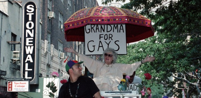 """E.G. Smith, left, and his mother, Norma Isaacs, 88, sitting under an umbrella with a sign that reads, """"Grandma For Gays,"""" ride past the site of the original Stonewall Inn in New York's Greenwich Village during the annual Gay and Lesbian Pride Parade on Sunday, June 25, 1989. A record 150,000 people marched down Fifth Avenue, commemorating the 20th anniversary of the Stonewall Inn riots which gave birth to the gay rights movement. (AP Photo/Sergio Florez)"""