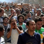 Egyptian mourners carry the coffin of Mohammed Darbaka, who was allegedly shot dead by a policeman over a payment dispute, during his funeral on Feb. 19 in Cairo.
