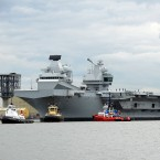 The HMS Queen Elizabeth, one of two brand-new British aircraft carriers, trails a collection of tug boats on the Firth of Forth in Scotland last month. U.K. Foreign Secretary Boris Johnson says the massive carriers, which have been billed as some of the biggest ships ever built for the Royal Navy, will sail through the disputed waterways of the South China Sea as a show of strength.