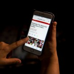 In this Monday, April 8, 2019, photo, a woman reads an article on her mobile phone concerning the chances of fake news in India during the upcoming elections in New Delhi, India. From manipulated pictures being picked up by mainstream news media, to misrepresented quotes sparking communal division, false news and hateful propaganda on digital platforms are at peak levels in the run-up to the Indian general elections.