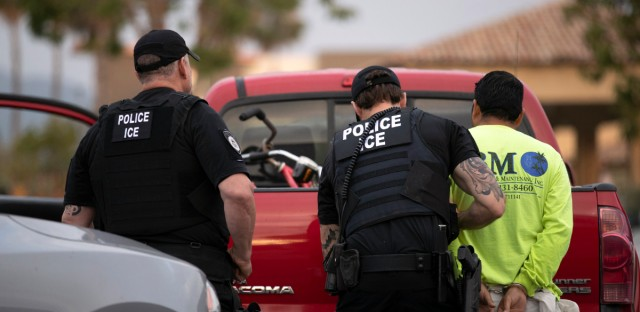 In this July 8, 2019 file photo, U.S. Immigration and Customs Enforcement (ICE) officers detain a man during an operation in Escondido, Calif.