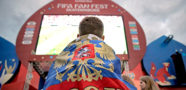 A boy covered in a Russian flag watches the opening match of the 2018 soccer World Cup, between Russia and Saudi Arabia, in the fan zone in Yekaterinburg, Russia, Thursday, June 14, 2018.