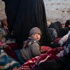 Women and children sit in the back of a truck as they wait to be screened by U.S.-backed Syrian Democratic Forces (SDF) after being evacuated out of the last territory held by Islamic State militants, in the desert outside Baghouz, Syria, Friday, March 1, 2019.