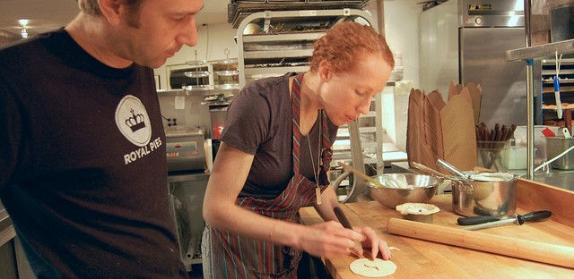 Art Jackson, left, watches Chelsea Kalberloh Jackson, cutting eel design into pie dough for lamprey pie at Pleasant House Bakery