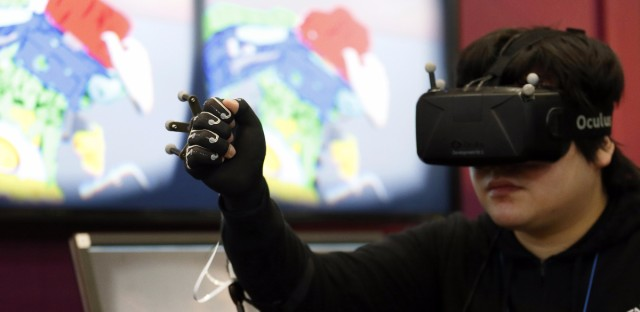 An attendant wearing an Oculus Rift virtual reality headset demonstrates a glove with a Yamaha Corp. rubber-like sensor at the Wearable Expo in Tokyo, on Jan. 13.