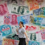 A woman walks by a money exchange shop decorated with different countries currency banknotes at Central, a business district in Hong Kong, Tuesday, Aug. 6, 2019. China's yuan fell further Tuesday against the U.S. dollar, fueling fears about increasing global damage from Beijing's trade war with President Donald Trump.