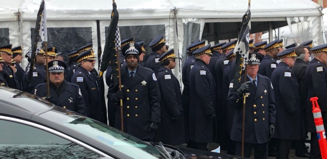 Chicago police officers stand at attention as the hearse approaches at the funeral of Officer Samuel Jimenez.