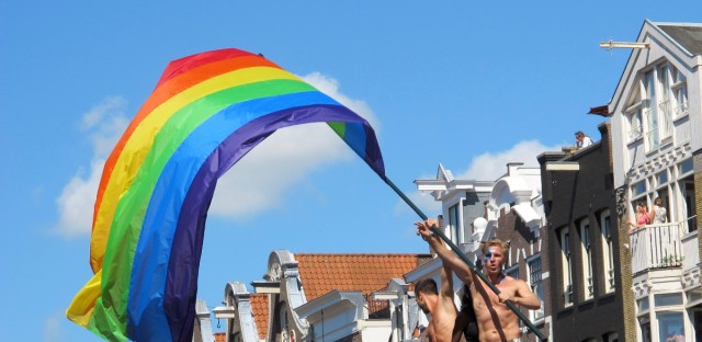 A participant waves a rainbow flag during the annual Canal Parade at Prinsengracht in Amsterdam, Saturday Aug. 3, 2013. Rainbow flags are flying from scores of buildings as tens of thousands of festival-goers, many dressed in pink or wearing studded leather, party it up at one of the city's biggest events: the annual Gay Pride celebration.