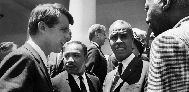 In this June 22, 1963, file photo, U.S. Attorney General Robert F. Kennedy, left, speaks with civil rights leaders, beginning second from left, Rev. Martin Luther King, Jr., head of the Southern Christian Leadership Conference; Roy Wilkins, executive secretary of the NAACP; and A. Phillip Randolph, president of Brotherhood of Sleeping Car Porters, on the White House grounds, in Washington, DC. Civil rights lawyer Joseph Rauh stands in the background at center.