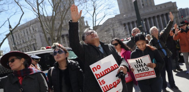 Local officials are promising a legal fight in the face of a block on grants from the Justice Department over immigration enforcement. Here, protesters pray outside the Immigration and Customs Enforcement office in New York City earlier this month.