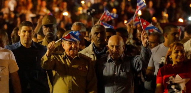 Cuba's President Raul Castro, center left, and Second Vice President Jose Ramon Machado Ventura, center right, wave flags as they take part in a march with torches to mark the 165th anniversary of the birth of Cuba's national independence hero Jose Marti and to pay tribute to late revolutionary leader Fidel Castro in Havana, Cuba, Saturday, Jan. 27, 2018.