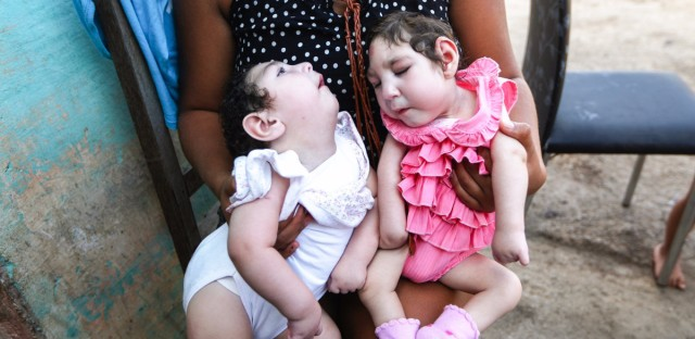A family member holds twins Eloisa (left) and Eloa, both 8 months old and born with microcephaly, during a Christmas gathering. The mother of the twins, Raquel, who lives in Brazil, said she contracted Zika during her pregnancy.
