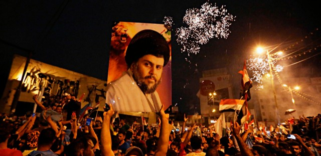 Supporters of Shiite cleric Muqtada al-Sadr carry his image as they celebrate in Tahrir Square, Baghdad, Iraq on Monday, May 14, 2018.