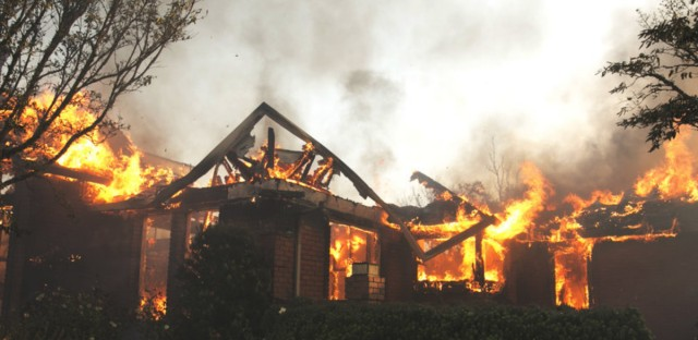 Flames from a wildfire consume a home Monday, east of Napa, Calif.