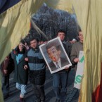 """Bucharest residents demonstrating to commemorate the victims of fights in Bucharest and Timisoara, carry a blood-smeared portrait of former Dictator Ceausescu in Bucharest Dec. 25, 1989. Picture taken through the Romanian national flag of which the communist party symbol was cut out. Text on portrait says; """"Ultimu Tiran, Ultimu Communistu"""" meaning: the last tiran, the last communist."""
