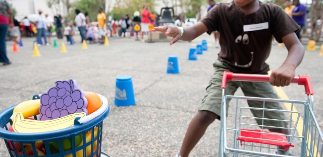 """A child runs a shopping cart relay during an Education Department summer enrichment event, """"Let's Read, Let's Move."""" The 2012 event was part of a summer initiative to engage youths in summer reading and physical activity, and provide them information about healthy, affordable food. Many efforts underway are aimed at getting people to think anew about their daily habits."""