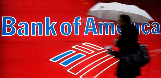 In this Dec. 7, 2011 photo, a woman passes a Bank of America office branch, in New York.