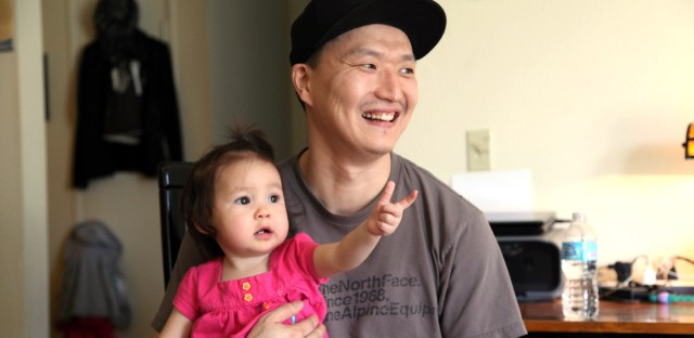 Korean adoptee Adam Crapser poses with daughter, Christal, 1, in the family's living room in Vancouver, Wash. on March 19, 2015. Crapser, whose adoptive parents neglected to make him a U.S. citizen, will face an immigration judge and could be separated from his family and deported to South Korea, a country he does not know.