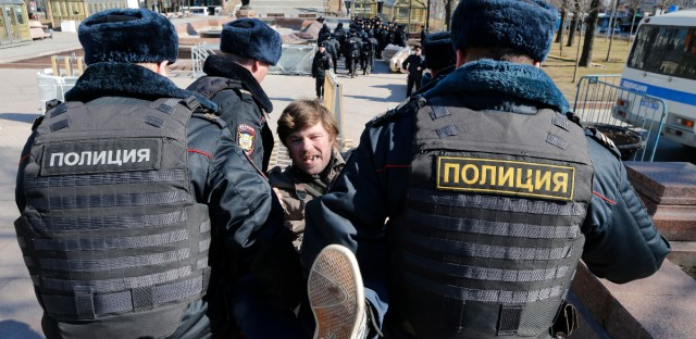 """Police detain a protester in downtown Moscow, Russia, Sunday, March 26, 2017. Russia's leading opposition figure Alexei Navalny and his supporters aim to hold anti-corruption demonstrations throughout Russia. But authorities are denying permission and police have warned they won't be responsible for """"negative consequences"""" or unsanctioned gatherings. (AP Photo/Alexander Zemlianichenko)"""