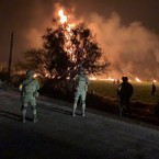 In this image provided by the Secretary of National Defense, soldiers guard the area by an oil pipeline explosion in Tlahuelilpan, Hidalgo state, Mexico, Friday, Jan. 18, 2019. A huge fire exploded at a pipeline leaking fuel in central Mexico on Friday, killing at least 21 people and badly burning 71 others as locals were collecting the spilling gasoline in buckets and garbage cans, officials said. Officials said the leak was caused by an illegal tap that fuel thieves had drilled into the pipeline in a small town in the state of Hidalgo, about 62 miles (100 kilometers) north of Mexico City.