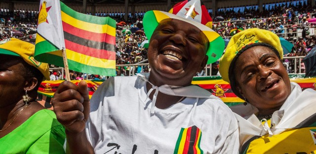 Zimbabweans sing and dance during a ceremony at a sports stadium in Harare marking the country's 36th independence anniversary.