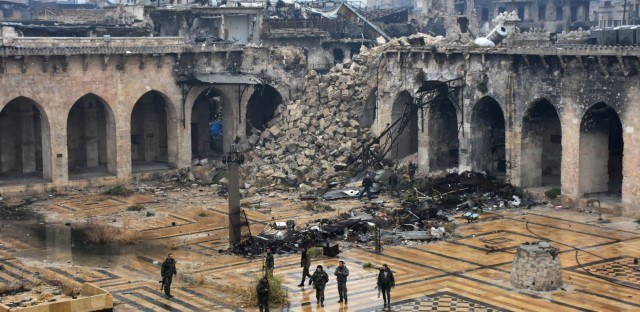 Syrian pro-government forces walk in the ancient Umayyad mosque in the old city of Aleppo on Tuesday, after they captured the area. After weeks of heavy fighting, regime forces were poised to take full control of Aleppo, dealing the biggest blow to Syria's rebellion in more than five years of civil war.