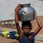 An Indian girl walks after collecting drinking water at a slum area in Mumbai, Maharashtra state, India, Saturday, April 30, 2016. Much of India is reeling under a weekslong heat wave and severe drought conditions that have decimated crops, killed livestock and left at least 330 million Indians without enough water for their daily needs. Rivers, lakes and dams have dried up in parts of the western states of Maharashtra and Gujarat, and overall officials say that groundwater reservoirs are at just 22 percent capacity.(AP Photo/ Rajanish Kakade )