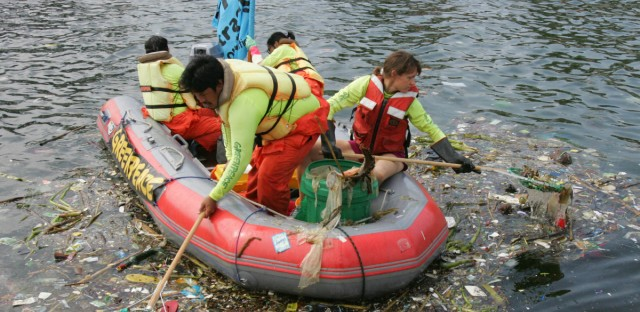 Greenpeace activists on an inflatable boat collect debris from the water mostly of plastics Wednesday, Aug. 16, 2006 in Manila Bay.