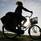 A woman rides a bicycle in Solo, Central Java, Indonesia, Tuesday, May 17, 2016.