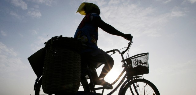 A woman rides a bicycle in Solo, Central Java, Indonesia.
