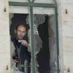 Palestinian Rev. Mitri Raheb talks to journalists from the bullet-shattered window of his apartment adjacent to the Evangelical Lutheran Christmas Church in the West Bank town of Bethlehem Saturday April 6, 2002. Rev. Raheb said in an interview Sunday April 7, 2002, that he was upset and sad that worshipppers were unable to attend Sunday mass because of a curfew imposed by the Israeli army.