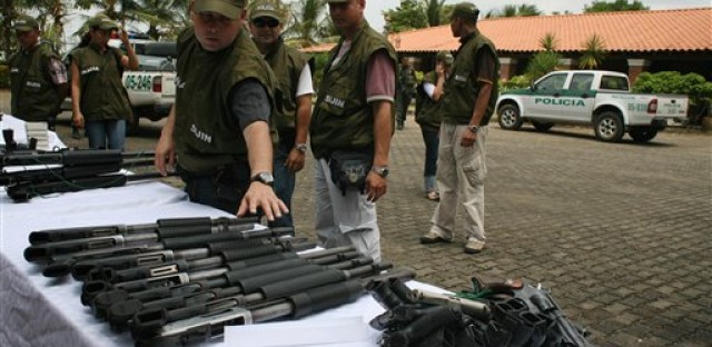 Police display seized weapons on property confiscated from former paramilitary boss and drug lord Carlos Mario Jimenez, alias 'Macaco,' in 2009.