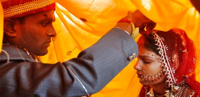 A groom puts red Sindoor powder on his bride's head as part of a ritual during a marriage ceremony in Allahabad, India.