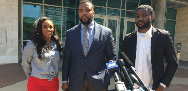 From left: K.C. Fox, Lee Merritt and Dominique Alexander stand outside of the Dallas Police Department headquarters on April 18, 2018.