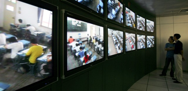 Officials from the Ministry of Education monitor examination halls through security cameras installed at the Wuhan No.2 Middle School in Wuhan, central China's Hubei province on Thursday, June 7 2007. Some 9.5 million students throughout China are taking part in the annual college entrance exam from a record 10.1 million students who signed up for the exam, scheduled for June 7-8, vying for about 5.67 million university places.