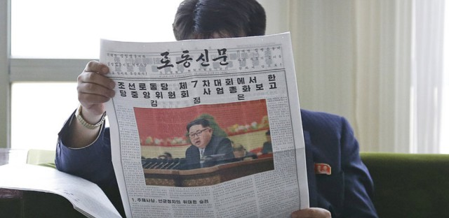 A North Korean man reads a local newspaper on Sunday with an image of leader Kim Jong Un. Kim said during a critical ruling party congress that his country will not use its nuclear weapons first unless its sovereignty is invaded, state media reported.