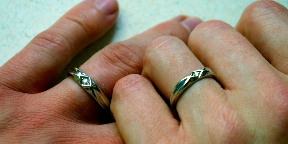 photo of two hands wearing rings