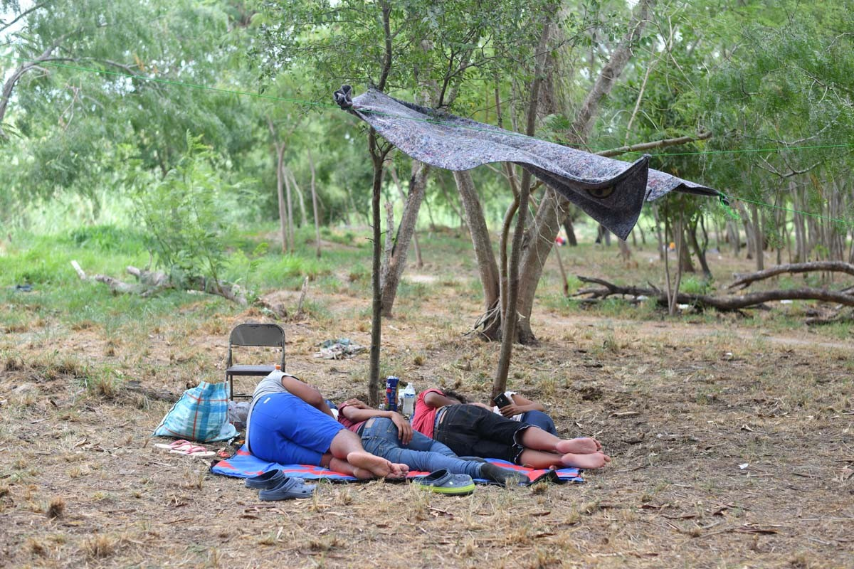 A few steps from the camp, migrants rest in an area close to the Rio Grande.