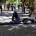 A protester takes a rest in a street leading to the sitin outside the Sudanese military headquarters, in Khartoum, Sudan, Tuesday, May 14, 2019. Sudanese protesters say security agents loyal to ousted President Omar al-Bashir attacked their sit-ins overnight, setting off clashes that left six people dead, including an army officer, and heightened tensions as the opposition holds talks with the ruling military council. Both the protesters and the transitional military council say the violence was instigated by al-Bashir loyalists from within the security forces.