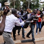 An activist opposed to the extension of presidential age limits is arrested and carried off by uniformed and plain-clothes police, while shouting for America and Israel to come to the rescue of Ugandans, near the Parliament building in Kampala, Uganda Thursday, Sept. 21, 2017. Ugandan police on Thursday fired tear gas to disperse protesters and arrested dozens of people opposed to plans to introduce legislation that could allow the longtime president Yoweri Museveni to extend his rule. (AP Photo/Ronald Kabuubi)