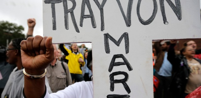 A protester carries a cross with the name of Trayvon Martin during a march to the Ferguson, Mo., police station on Oct. 13, 2014.