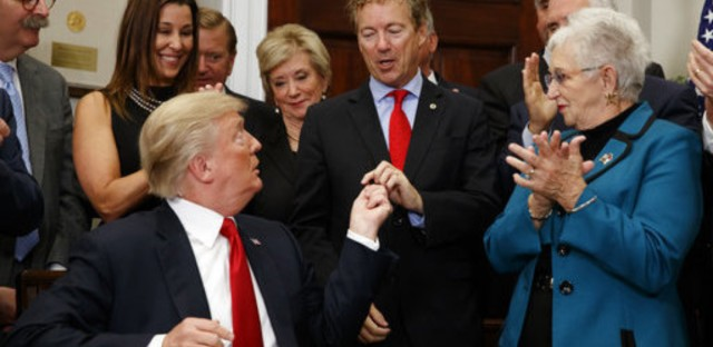 President Trump hands a pen that he used to sign an executive order on health care to Sen. Rand Paul, R-Ky., in the Roosevelt Room of the White House on Thursday.
