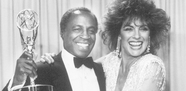 Actor Robert Guillaume, star of Benson, gets a hug from Linda Gray of Dallas, who presented him with the 1985 Emmy for outstanding lead actor in a comedy series, in Pasadena, Calif. Guillaume was the first African-American to win the award.