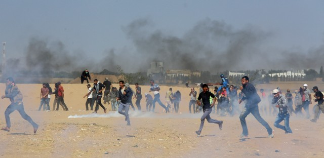 Palestinian protesters run for cover from teargas fired by Israeli troops near the border, east of Khan Younis, in the Gaza Strip, Tuesday, May 15, 2018.