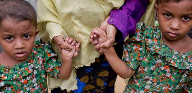A Rohingya Muslim woman, who crossed over from Myanmar into Bangladesh, holds the hands of her grandchildren at Balukhali refugee camp in Ukhiya, Bangladesh, Wednesday, Nov. 15, 2017.