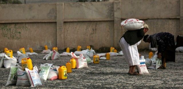 Yemeni men carry food supplies provided by a local charity to conflict-affected Yemenis in Sanaa, Yemen, Monday, June 27, 2016. (AP Photo/Hani Mohammed)